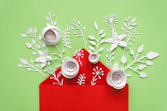 Opened red envelope full of varios white paper flowers on green background Royalty Free Stock Photos