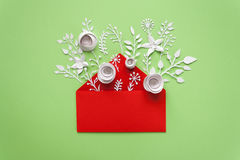 Opened red envelope full of varios white paper flowers on green background Royalty Free Stock Photo