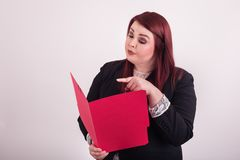 Opened red folder held by redheaded young professional woman pointing at file folder stock photo