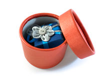 Opened red gift box with surprise in it. Opened round red gift box with surprise in it: blue little box with rag flower Royalty Free Stock Photography
