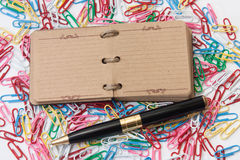 Opened retro notebook and golden pen with colored paperclips Royalty Free Stock Photography