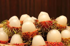 Opened rind of rambutan. See white pulp among red hairy skin of rambutans royalty free stock image
