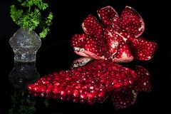 Opened ripe pomegranate reflected on black royalty free stock photos