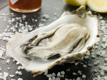 Opened Rock Oyster with Hot Chilli Sauce Stock Photography