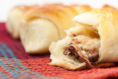 Opened roll with chocolate cream on the kitchen tablecloth Royalty Free Stock Photography