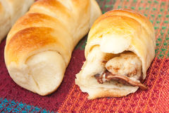 Opened roll with chocolate cream on the kitchen tablecloth Stock Images