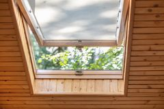 Opened roof window with blinds or curtain in wooden house attic. Room with slanted ceiling made of natural eco materials. And park view through opened window stock image