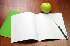 Opened school notebook, felt-tip pens and apple. Opened school notebook, felt-tip pens and green apple on table royalty free stock photos