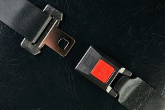 Opened seat belt on black leather background. Close-up. Safety concept Stock Images