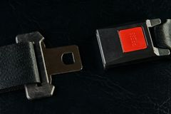 Opened seat belt on black leather background. Close-up. Safety concept Stock Photos