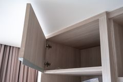 Opened small wooden cabinet under white ceiling in room. stock photo