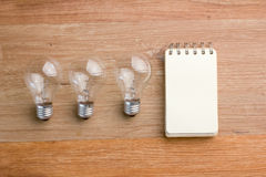 Opened spiral notebook with light bulb Stock Images