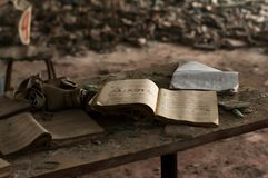 Opened study book and gas mask on wooden table in front of rexf with respirators royalty free stock images