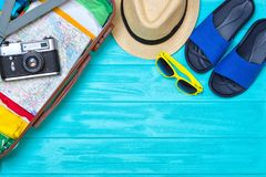 Opened suitcase with beach accessories on a wooden background. stock photo