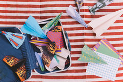 Opened Suitcase with Color Paper Planes on The White and Red Stripes Mat.  royalty free stock photos
