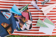 Opened Suitcase with Color Paper Planes on The White and Red Stripes Mat.  stock photo