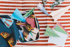 Opened Suitcase with Color Paper Planes on The White and Red Stripes Mat.  royalty free stock image