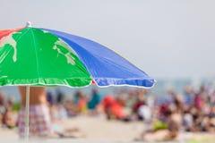 Opened sun umbrella on sandy beach Stock Photos