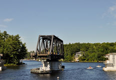 Opened swing bridge with boats passing Stock Photo