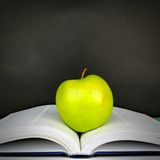 Opened textbook with apple in front of a chalkboard Royalty Free Stock Photography