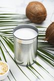 Opened tin can with coconut milk drink. Alternative non dairy vegan milk on white stone table Royalty Free Stock Photos