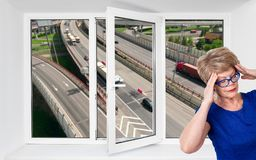 Opened triple-casement pvc window with noisy highway outdoor and senior woman with headache inside room. Opened triple-casement pvc window with noisy highway stock photography