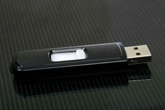 Opened usb stick. On a black and grey striped laptop Stock Photos