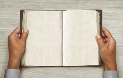 Opened vintage book. Male hands and opened vintage book over table Royalty Free Stock Photography