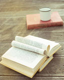 Opened vintage book on the wooden table with old fashioned cup of tea. The page in the form of heart. Side view. The toning. Royalty Free Stock Image