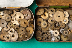 Opened vintage box with aged grunge gears collection set. macro, green paper background. Shallow depth of field, soft Royalty Free Stock Photography