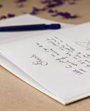 Opened wedding guest book with a pen. Opened wedding guest book with writing and a pen on a beige background Stock Images