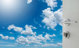 Opened white door to beautiful sky with clouds Stock Photo