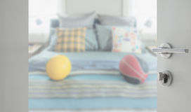 Opened white door to beddroom with decorative pillow and football on bed Royalty Free Stock Photography