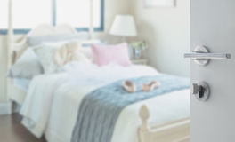 Opened white door to bedroom with pillows and doll on white bed Royalty Free Stock Photography