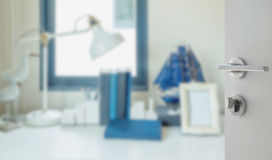 Opened white door to blur image of work table with lamp,pencil,book Stock Photos