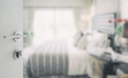 Opened white door to blurred background of modern bedroom Stock Photos