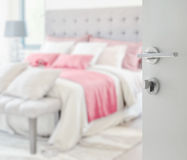Opened white door to blurred colorful pillows on bed Royalty Free Stock Images