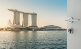 Opened white door to blurred skyline of singapore cityscape Royalty Free Stock Images