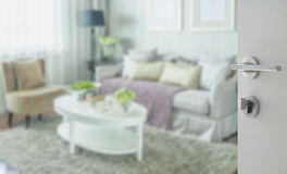Opened white door to classic living room interior with sofa Stock Images
