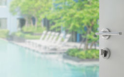 Opened white door to swimming pool with beach chairs. นื pool deck royalty free stock photos