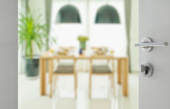 Opened white door to wooden dining table and chairs Stock Photos