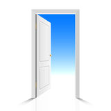 Opened white door with view on clear sky Royalty Free Stock Photography