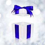 Opened white gift box with blue bow on twinkling background. Opened white gift box with blue satin bow on a twinkling silver background Royalty Free Stock Photos