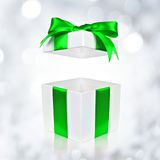 Opened white gift box with green bow on twinkling background Stock Photo