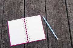 Opened white page of blank realistic spiral notepad notebook and blue pencil on wood texture background Stock Images
