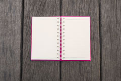 Opened white page of blank realistic spiral notepad notebook on wood texture background. Vintage style Royalty Free Stock Images