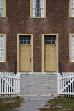 Opened white picket fence gate leads to two yellow antique doors. Stock Images