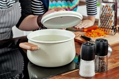 Opened white saucepan with wood pens on the black stove and glass spice mill in the kitchen room. Cooking a soup, preparation. Opened white saucepan with wood royalty free stock images