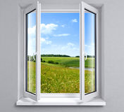 Opened window. View to green field and sky Royalty Free Stock Photos