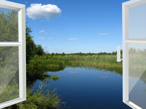 Opened window to the lake and meadow Stock Photo